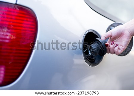 Female hand holding fuel filler cap  - stock photo