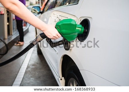 Female hand holding green pump filling gasoline - stock photo