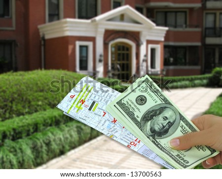 Female hand holding key and map in front of a house - stock photo