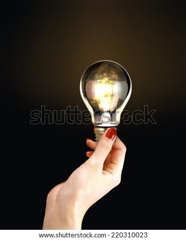 Female Hand Holding Light Bulb - stock photo