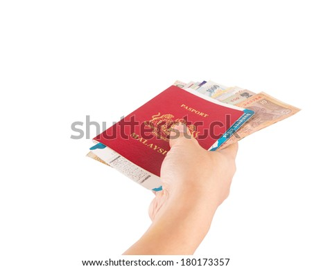 Female hand holding Malaysian passport with various currency and airplane boarding pass . - stock photo