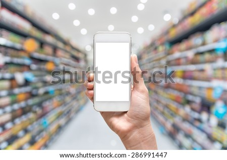 Female hand holding mobile smart phone on Supermarket blur background, business concept - stock photo