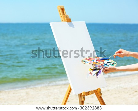 Female hand holding palette with paints and easel with canvas on beach - stock photo