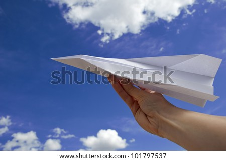 Female hand holding paper airplane against blue sky - stock photo