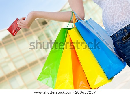 Female hand holding shopping bags and credit card - stock photo