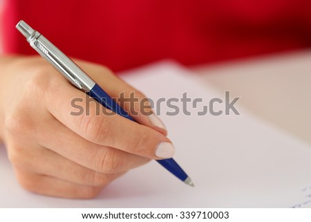 Female hand holding silver pen closeup. Woman writing letter, list, plan, making notes, doing homework. Student studying. Education, self development and perfection concept - stock photo