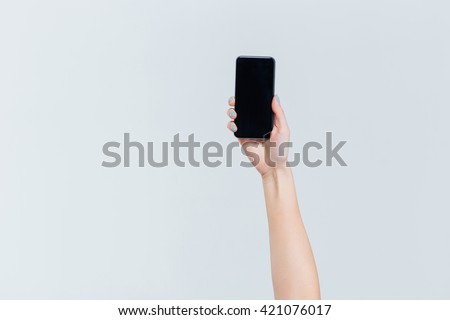 Female hand holding smartphone with blank screen isolated on a white background - stock photo