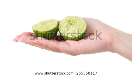Female hand holding two pieces of lime isolated on white - stock photo