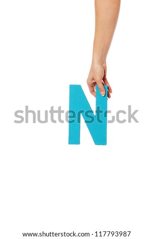 Female hand holding up the uppercase capital letter N isolated against a white background conceptual of the alphabet, writing, literature and typeface - stock photo
