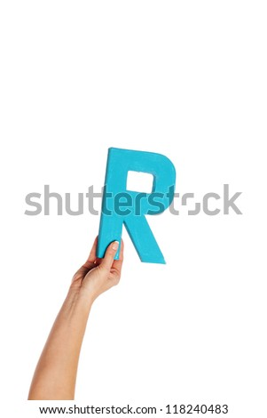 Female hand holding up the uppercase capital letter R isolated against a white background conceptual of the alphabet, writing, literature and typeface - stock photo