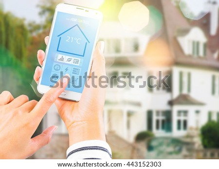 Female hand holding white mobile smart phone with smart home application on the screen. Blurred house on the background. For access to all of the controls of your house and caring of home security.  - stock photo