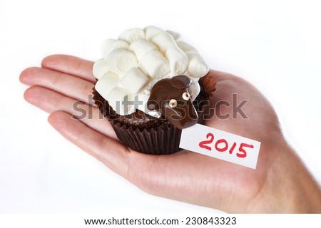 Female hand holds cake lamb as simbol 2015 new years isolated on white background - stock photo