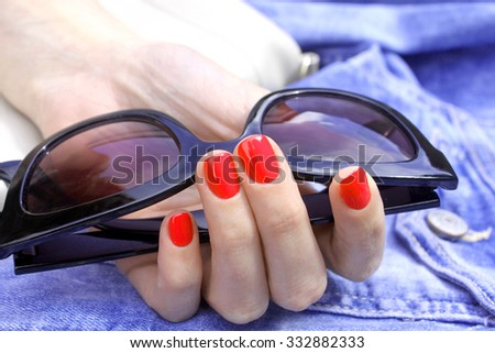 Female hand holds sunglasses with pink nails on jeans - stock photo
