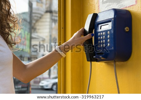 Female hand holds up the phone. Calling from city payphones. - stock photo