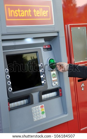 Female hand inserting a bank card at an automatic bank teller machine - stock photo
