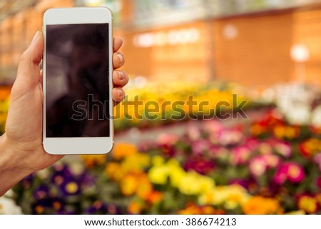 Female hand is holding a smart phone, flowers in orangery in the background - stock photo