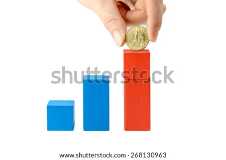 Female hand is holding US dollar coin above red  wooden cube on a white  background. The first cube is blue and low, the second is blue and higher. On the last red cube is added the  US dollar coin.  - stock photo