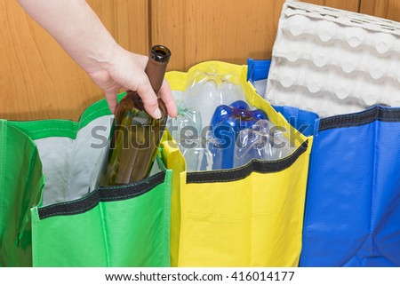 Female hand is sorting empty wine bottle to the green bag. Household Waste concept. - stock photo