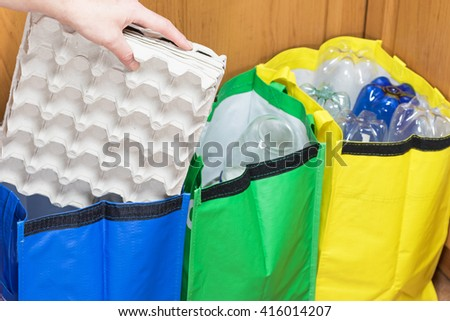 Female hand is sorting paper packaging for eggs to the blue bag. Household Waste concept. - stock photo