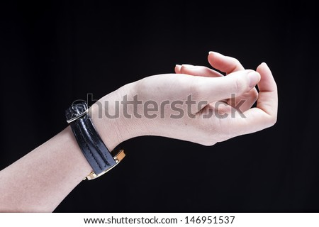 Female hand, isolated on a black background, is wearing a wrist watch - stock photo