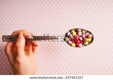 female hand keeping a silver spoon with edible decorations for cupcakes - stock photo
