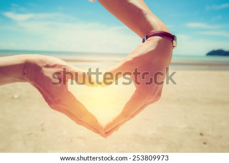 Female hand make heart shape on beach. Vintage filter. - stock photo