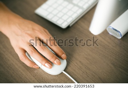 Female hand on a computer mouse - stock photo