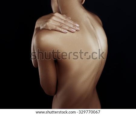 Female hand on her shoulder. Dark background - stock photo