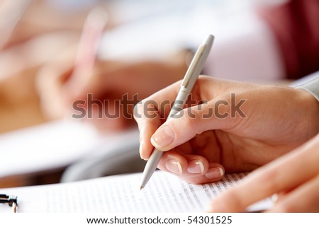 Female hand over paper making notes at seminar - stock photo