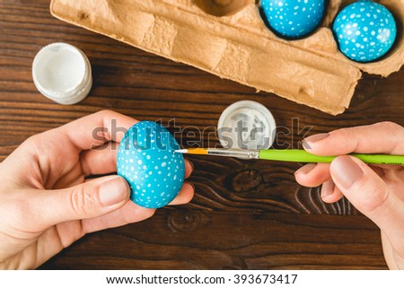 Female hand painted Easter eggs with a brush, top view - stock photo