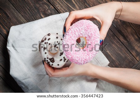 Female hand picking sweet sugary donut from rustic wooden kitchen table, tasty bakery doughnuts overhead shot, top view - stock photo