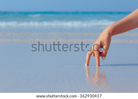 Female hand playing in the water on the white sand beach on blue sea background - stock photo