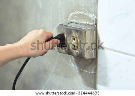 female Hand pull old socket  - stock photo