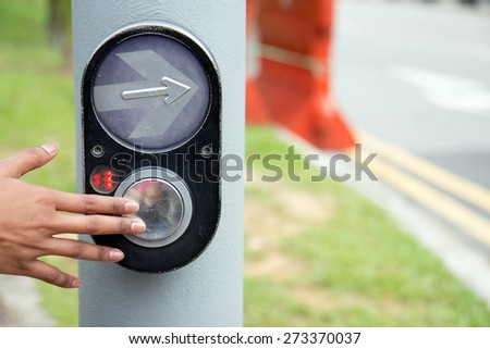 female hand pushing button for traffic light. Use traffic lights at the crossroads. Button of the mechanism lights traffic lights on the street. System control traffic light intersection close. - stock photo