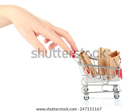Female hand pushing small shopping cart with bags, isolated on white - stock photo