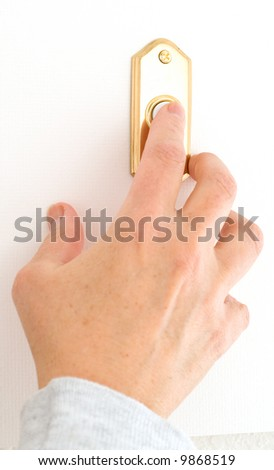 Female Hand Pushing the Doorbell Buzzer - stock photo