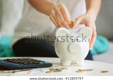 Female hand putting coin into piggy bank closeup - stock photo