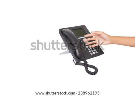 Female hand reaching for desktop telephone handset over white background  - stock photo