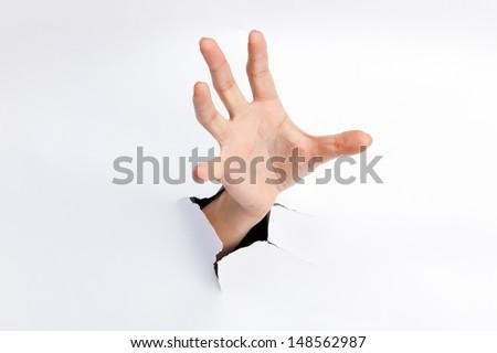 Female hand reaching through torn paper sheet - stock photo