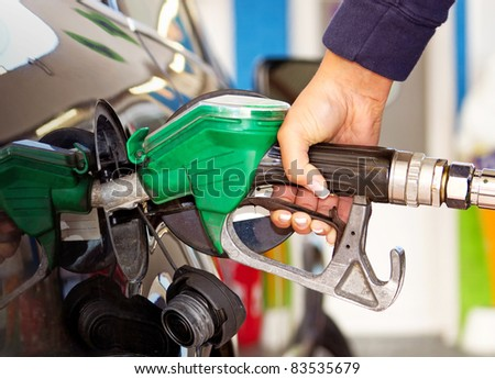 Female hand refilling the car with fuel - stock photo