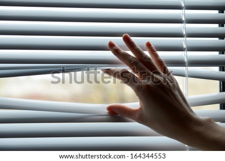 Female hand separating slats of venetian blinds with a finger to see through - stock photo