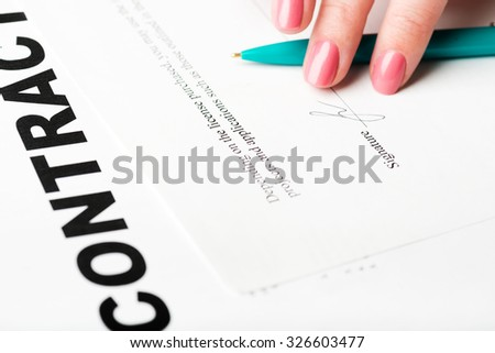 female hand signing a contract. - stock photo