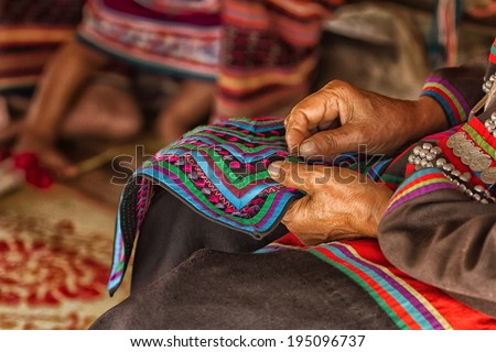 Female hand stitching cloth to make ancient Thai pattern fabric - stock photo