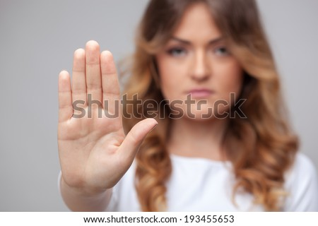 female hand stop sign on grey background - stock photo