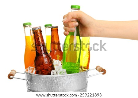 Female hand taking glass bottle of drink from metal bucket isolated on white - stock photo