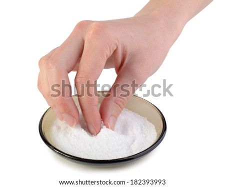 Female hand taking salt from glass bowl, isolated on white. - stock photo