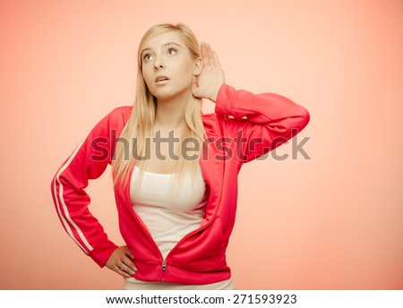 Female hand to ear listening. Gossip teen girl with palm behind ear spying. Young sporty woman listening secret. - stock photo