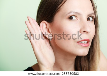 Female hand to ear listening on green. Gossip girl with palm behind ear spying. Young business woman listening secret. - stock photo