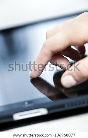 Female hand touching tablet computer screen with finger - stock photo