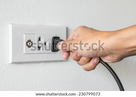 Female hand trying to plugging in appliance to electrical outlet in wall  - stock photo